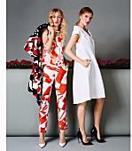 Zwei Frauen in elegantem Outfit mit Hosenanzug im Pop-Art Look und weißem Kleid