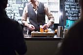 Barkeeper mixt Cocktails beim Schlachtfest-Dinner in einer Markthalle (Berlin)