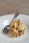 A cupcake with buttercream spaghetti and sauce