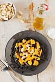 Black tagliatelle with pumpkin sauce and cashew nuts