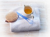 A towel, a brush and a jug of oil