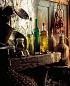 Bottles of oils, copper pots, jugs and spices in a rustic kitchen