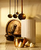 A chef's hat, copper pots, ladles and garlic