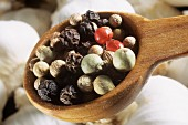 Red, white, green, and black pepper berries on a wooden spoon