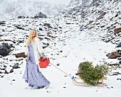 Blonde Frau im Abendkleid mit Allover-Pailletten und Kurzmantel aus Kunstfell zieht Schlitten mit Tannenbaum im Schnee