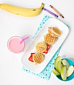 Waffles with fruit, a milkshake and fruit as a snack for children