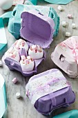 Eggshells full of mini marshmallows in decorative egg boxes