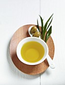 A bowl of olive oil, green olives and a spring of olive leaves