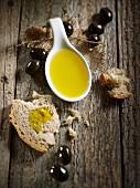 A spoonful of olive oil, bread and black olives on a wooden surface
