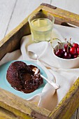 Warm chocolate lava cake, with fresh cherries and lemonade on a tray