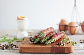 Green asparagus wrapped in ham with soft boiled eggs