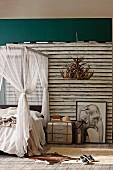 Afrika im Schlafbereich - Himmelbett mit Stoffbaldachin neben Metall-Nachtkästchen und Zeichnung vom Elefant vor Bretterwand, Kerzenleuchter aus Geweihen von Decke abgehängt