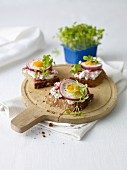 Slices of bread topped with ham salad, fried eggs and cress