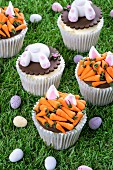 Various Easter cupcakes on a grass surface