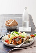 Marinated chicken legs with herbs, salad and bread