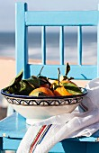 Oranges in a ceramic bowl on a light-blue chair by the sea
