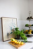 Sliced yellow pepper on wooden board, potted herbs, and fruits and vegetables on silver cake stand