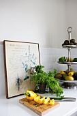 Aufgeschnittene Paprikaschote auf Holzbrett, Kräutertopf neben Silber Etagere mit Früchten und Gemüse