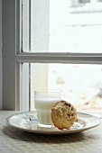A chocolate chip cookie and a glass of milk in front of a window