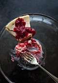 A slice of cheesecake with raspberry sauce on a glass plate with a fork with a bite taken out