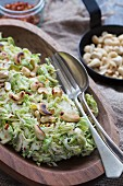 Brussels sprouts salad with roasted cashew nuts in a wooden bowl