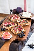 Gorgonzola sandwiches with figs and grapes on a wooden chopped board