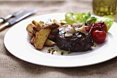 Rump steak with potato wedges and cherry tomatoes