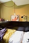 Schwarze Ablagefläche mit Tischleuchte und gerahmtem Bild an senfgelbe Wand gelehnt, davor Bett mit gelber und lilafarbener Decke