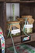 Home-made herb salts in preserving jars on dresser shelf