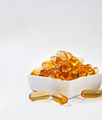 Fish oil capsules in a porcelain bowl against a white background