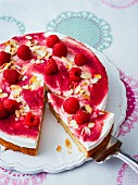 Cream cheese cake with raspberry sauce and flaked almonds