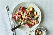 Pink cauliflower and avocado salad with pine nuts (seen from above)