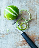 A lime with zest and a zest peeler