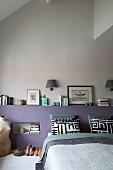 Modernes Schlafzimmer mit mauvefarbenem Bettkopfteil, Bücherstapel, schwarz-weißen Kissenbezügen und Vintage-Schneiderpuppe