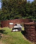 Geschwungener Zaun aus Geflecht um Sonnenliege im Garten