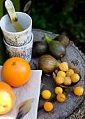 Frisches Obst und Becherstapel auf Baumstamm-Tisch im Freien