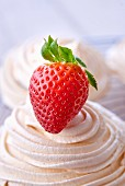 A meringue decorated with a strawberry (close-up)