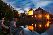 Wasserschloss Gesmold in the evening with the reflection shimmer in the moat which is fed by the River Else