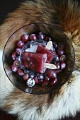 Red grape ice lollies in a glass bowl on an animal fur