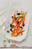A baby carrot salad with feta cheese, olives and mint