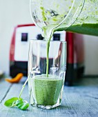 A seaweed and chicory smoothie with hemp seeds, chickweed, basil and parsley being poured into a glass