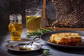 Honey in a jar with rosemary, and honeycomb on a vintage plate