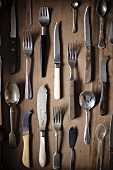 Various items of vintage cutlery on a wooden surface
