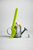 Pastel sugar eggs in a mini watering can and green fork