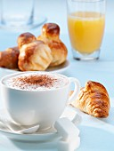 A cappuccino, a croissant, brioche and a glass of orange juice