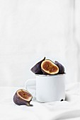 Halved fresh figs in a cup and next to it