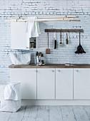 Weisser Unterschrank, Hakenleiste mit Spülbürsten, davor von Decke abgehängte Holzleisten im Waschraum, an der Wand Tapete mit Backsteinmuster