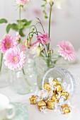 Goldene Bonbons und rosa Blumendeko am Buffet