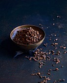 Cloves in a bowl and next to it on a dark surface