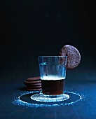 A glass of coffee with a chocolate biscuit on the rim